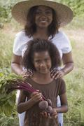 African mother and daughter holding beets in garden Stock Photos