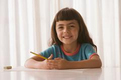 Hispanic girl with paper and pencil Stock Photos