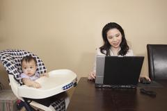 Kiinalainen äiti työskentelee kannettavan tietokoneen vieressä vauva syöttötuoli Kuvituskuvat