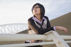 Hispanic woman leaning on urban railing Stock Photos