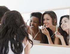 Friends applying makeup in mirror Stock Photos