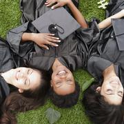 Friends in caps and gowns laying in grass Stock Photos