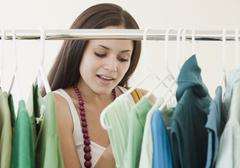 Mixed race woman shopping in clothing store Stock Photos