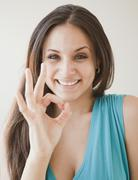 Mixed race woman making ok symbol Stock Photos