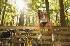 Hispanic cyclist sitting on bridge railing Stock Photos