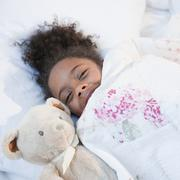 Mixed race girl in bed with teddy bear Stock Photos
