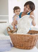 """""""hispanic mother holding daughter, talking on phone and doing laundry"""" Stock Photos"""
