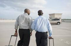 Stock Photo of african businessmen pulling luggage in parking lot