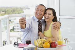 Hispanic couple taking self-portrait with cell phone Stock Photos