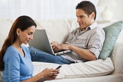 Hispanic couple with laptop and cell phone in living room Stock Photos