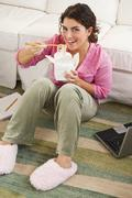 mixed race woman eating take-out - stock photo