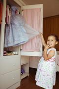 Hispanic girl taking costume from closet Stock Photos