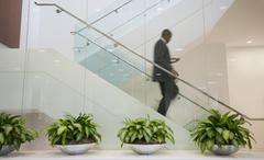 African american businessman descending staircase Stock Photos