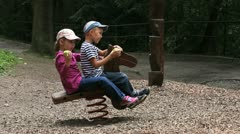 Children ride a wooden horse and eat apples Stock Footage