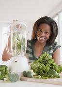Mixed race woman blending vegetables Stock Photos