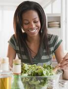 Mixed race woman tossing salad Stock Photos