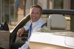 caucasian businessman smiling in convertible - stock photo