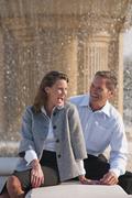 Caucasian couple laughing near spraying fountain Stock Photos