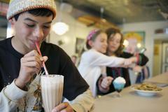 Mixed race boy drinking milkshake in cafe Stock Photos