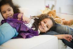Hispanic sisters in costumes sleeping on couch Stock Photos