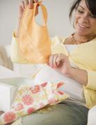 Pregnant hispanic woman looking at baby bib Stock Photos
