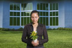 Mixed race woman holding flowers in pot Stock Photos
