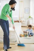 Mixed race mother sweeping floor Stock Photos