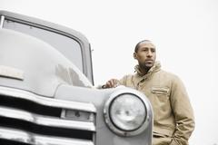 african american man standing next to old-fashioned truck - stock photo
