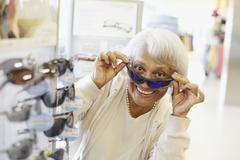Vanhempi afrikkalainen amerikkalainen nainen yrittää aurinkolasit Kuvituskuvat