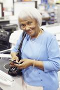 Senior african american woman text messaging on cell phone Stock Photos