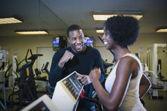 Personal trainer motivating woman on treadmill Stock Photos