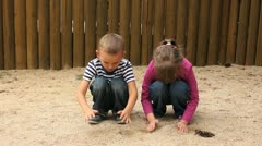Children strew sand through hands Stock Footage