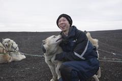 Kiinalainen mies hyväily koira koiravaljakolla pack Kuvituskuvat