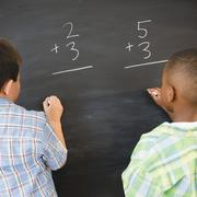 Boys solving math problems on blackboard Stock Photos