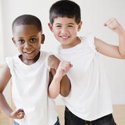 smiling boys flexing biceps - stock photo
