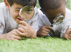 boys looking at grass through magnifying glasses - stock photo