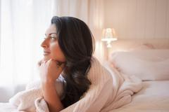 Middle eastern woman laying on bed thinking Stock Photos