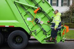 Pacific islander man riding on garbage truck Stock Photos