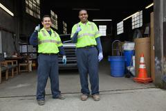 sanitation workers giving thumbs up in garage - stock photo