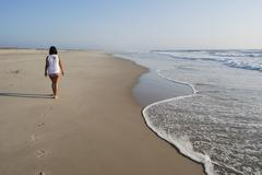 Stock Photo of Girl walking in the beach