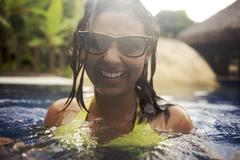 Mixed race woman wearing sunglasses in swimming pool Stock Photos
