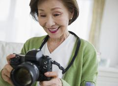 japanese woman holding digital camera - stock photo