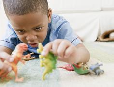 Afrikkalainen amerikkalainen poika makaa lattialla leikkii lelu dinosaurukset Kuvituskuvat