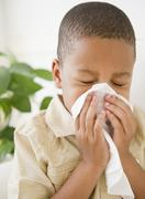 African american boy sneezing into tissue Stock Photos