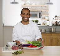 Mixed race chef holding plate of vegetables Stock Photos
