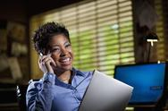 Stock Photo of black businesswoman in office using cell phone