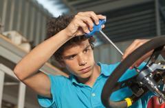 Hispanic teenager working on go-cart Stock Photos