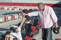 Hispanic grandfather and grandson on go-cart track Stock Photos