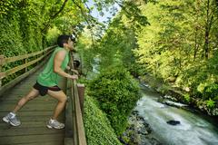Mixed race runner stretching on walkway near river Stock Photos