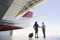 Hispanic business people meeting in airplane hangar Stock Photos